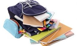 Blue backpack overflowing with various school supplies including notebooks, pens, pencils and calculator.